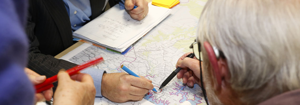 A group of people examining a District Map