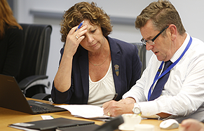 Photo of Heather Nesbitt and Geoff Roberts examining a document during a meeting