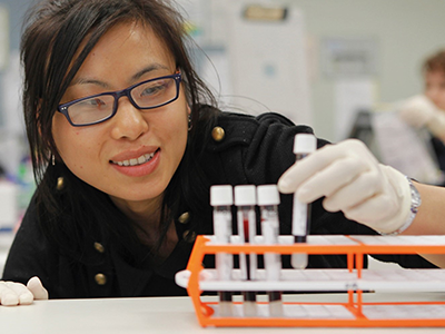 A female scientist looking at test tubes
