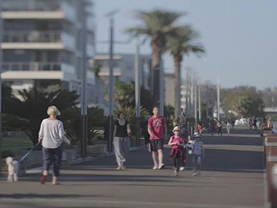 People walking along a waterfront pathway alongside a medium density development