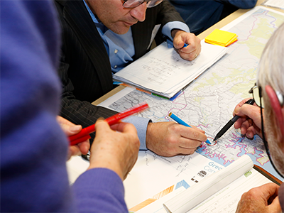 A close up of three people making notes on a district map during a community consultation session.