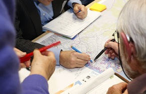 A group of people examining a District Map at a community session