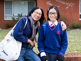 A smiling mother and daughter wearing a school uniform sitting on the fence in front of a 1960s red brick apartment building.