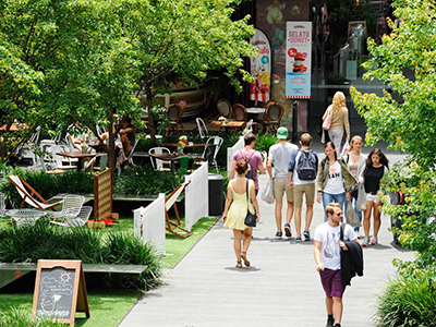 People walking through an open air cafe on a sunny day