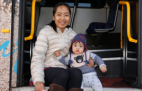 A woman and young girl on the steps of a Talk bus at a community consultation event.
