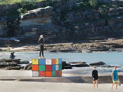 A woman standing upon an oversized sculpture of a Rubik's Cube on Maroubra beach.