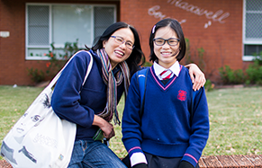 A smiling mother and her daughter wearing a school uniform sitting on the fence in front of a 1960s red brick apartment building.