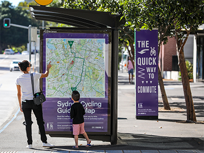 A woman and boy looking at a map of cycling routes on a bus shelter